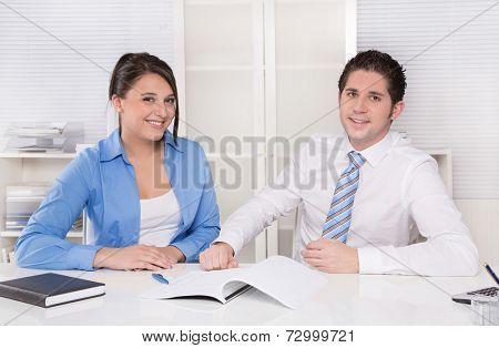 Teamwork - young business colleagues in a meeting discussing