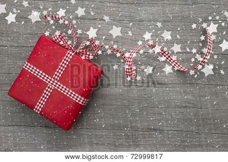 Christmas Present wrapped in red paper on a wooden background for a voucher coupon - greeting card country style
