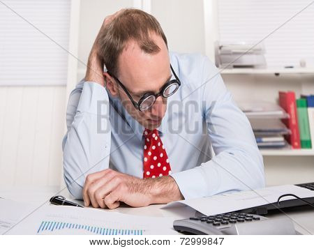 Overworked and tired businessman with glasses reading at desk