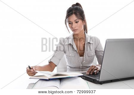 Unhappy young woman sitting at desk - isolated on a white background - with laptop and reading a book