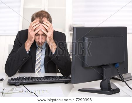 Overworked businessman frustrated and stressed in his office with computer - overtime.