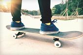 stock photo of skateboarding  - young woman skateboarder legs skateboarding at skatepark - JPG