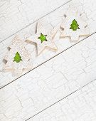 picture of linzer  - Overhead view of 3 Christmas linzer cookies with green jelly aranged diagonally on white painted background - JPG