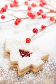 stock photo of linzer  - Christmas Tree Linzer cookie with powdered icing sugar and red decorations in the background.