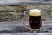 stock photo of stein  - Horizontal image of a glass stein filled with dark draft stout beer on rustic wood - JPG