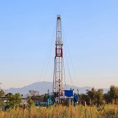 stock photo of  rig  - Oil Land Drilling Rig Working In The Field For Petroleum Exporation at Sunset Time