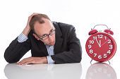 stock photo of sabbatical  - Businessman overworked with red clock isolated on white background - JPG