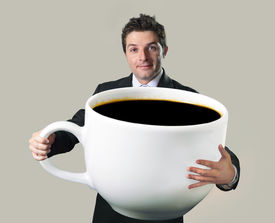 image of addicted  - young happy business man holding a funny huge and oversized cup of black coffee in caffeine addiction concept isolated on even background - JPG