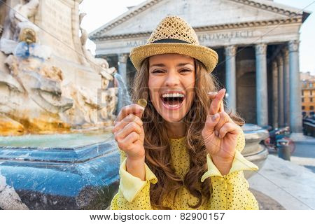 Happy Young Woman With Crossed Fingers And Coin Near Fountain Of