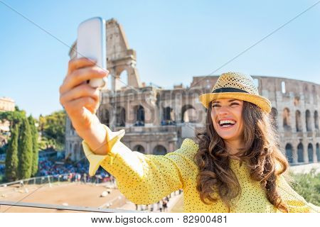 Smiling Young Woman Taking Photo With Cell Phone In Front Of Col
