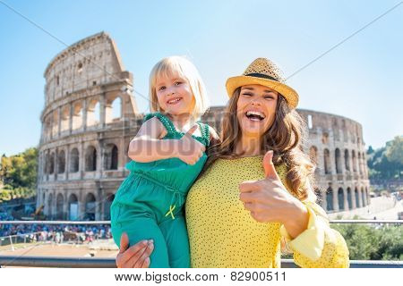 Happy Mother And Baby Girl Showing Thumbs Up In Front Of Colosseum In Rome, Italy
