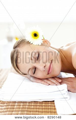 Blond Young Woman With Flowers In Her Hair With Closed Eyes In A Spa Center