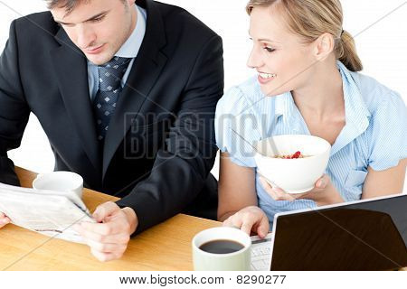 Happy Couple Of Businesspeople Having Breakfast Reading The Newspaper