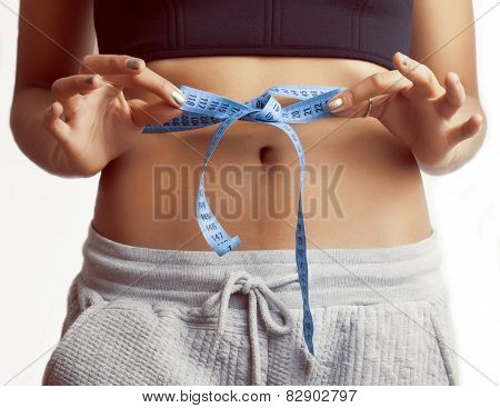 woman measuring waist with tape on knot like a gift, african tan