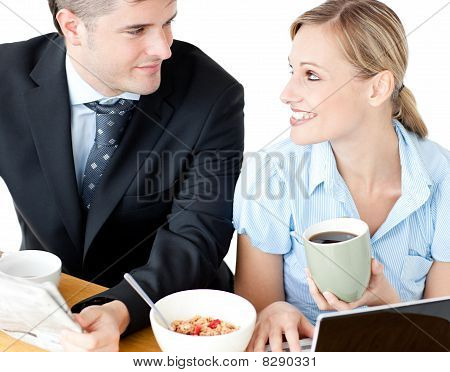 Affectionate Young Couple Having Breakfast Using Their Laptop