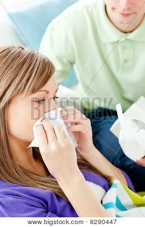 Sick Woman With Tissue Lying On A Sofa