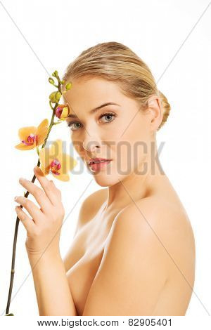 Topless woman with an orange orchid flower.