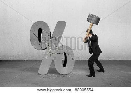 Businessman Holding Sledgehammer Hitting Cracked Percentage Sign With Concrete Room