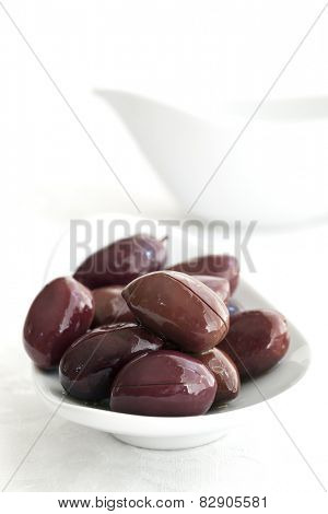 Black olives in small white dish.