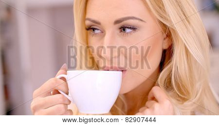 Attractive blond woman enjoying a hot beverage holding a cup of tea or coffee in her hand as she smiles at the camera
