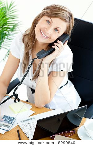 Self-assured Businesswoman Talking On Phone Sitting At Her Desk