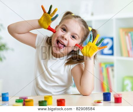 Girl having fun, her palms covered with paint