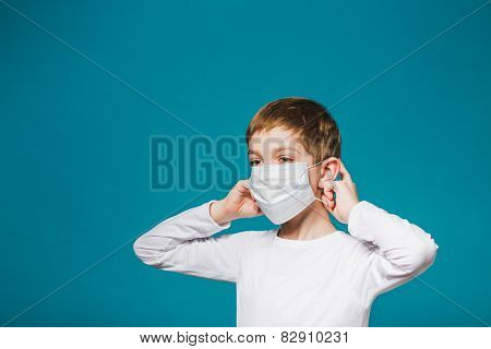 Boy Putting On Protection Mask Over Blue Background