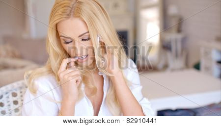 Close up Pretty Blond Woman Calling Through her Mobile Phone While Biting her Finger Nail
