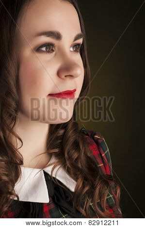 Cute Brunette In Tartan Dress With Red Lips And Curles. Studio Portrait