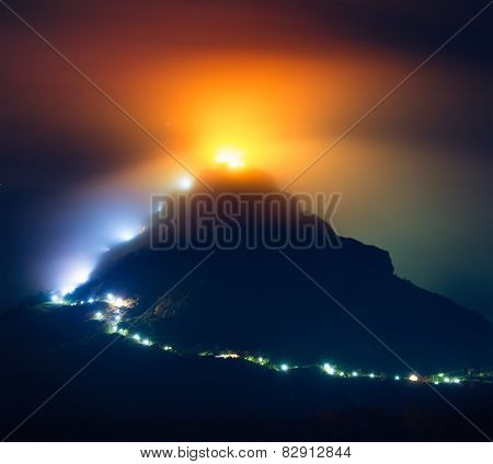 Mountain Adam's Peak (Sri Pada) covered by thick fog highlited by illumination of the temple and lamps along the way to top. Sri Lanka