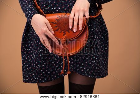 Closeup image of a female hands holding bag over brown background