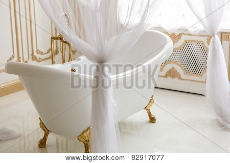 White Bath With Baldachin Next To Big Window