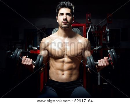 Young Man Doing Heavy Weight Exercise In Gym.