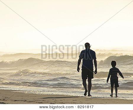 Padre e hijo caminar en la playa al amanecer