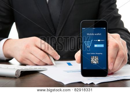 Businessman At The Office Holding A Phone With Onlain Shopping On The Screen