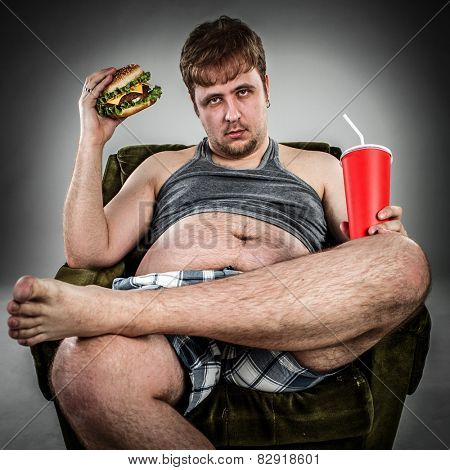 Fat man eating hamburger seated on armchair. Style fast food.