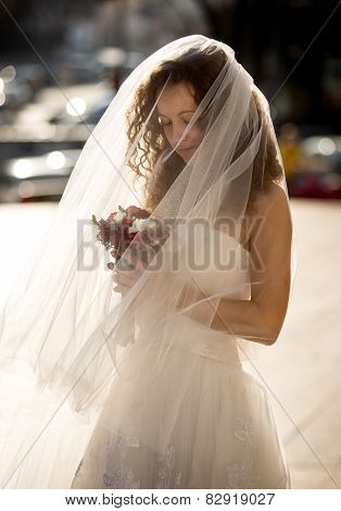Cute Curly Bride With Long Veil Looking At Bouquet