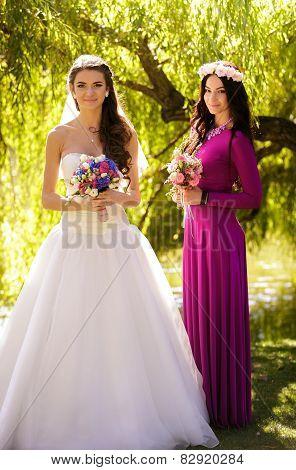 Brunette Bride Posing With Bridesmaid In Long Dress Posing At Park