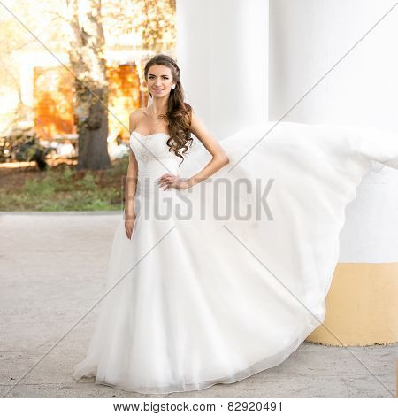 Brunette Bride In Long White Dress Posing At Windy Day At Park
