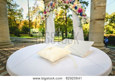 Wedding Rings Lying On Cushion At Decorated Table
