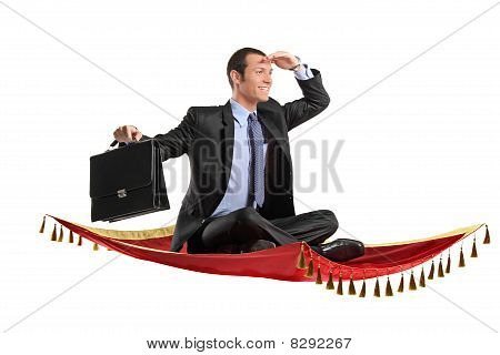 A businessman holding a suitcase while flying on a carpet