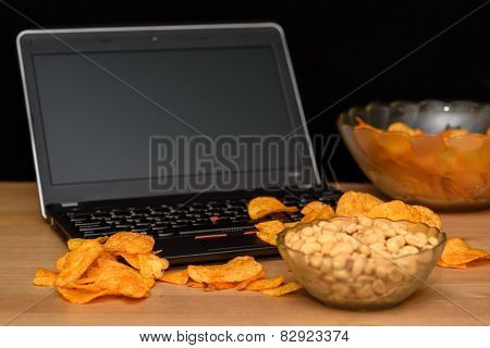 Open Laptop With Chips Scattered On Keyboard Isolated On Black Background