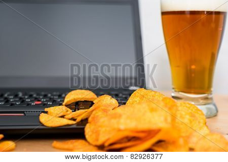 Closeup Of Open Laptop With Chips Scattered On Keyboard And Glass Of Beer In Background
