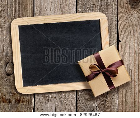 Blackboard And Gift Box On Wooden Background