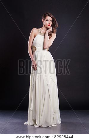 Beautiful attractive  young woman in elegant fashion dress posing over black wall.