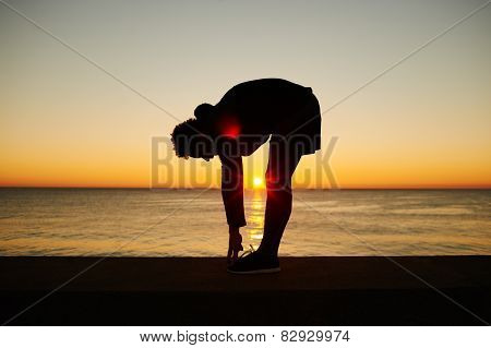 Young Muscular Build Man Doing Stretching Exercise On The Beautiful Sea Background During Sunset
