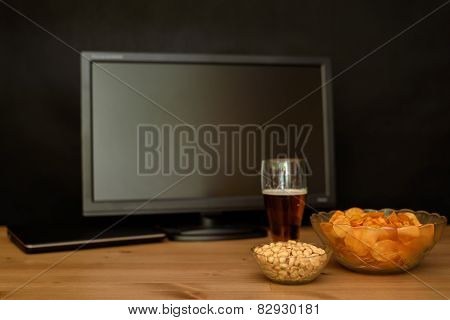 Tv And Computer With Unhealthy Snack On Table Isolated On Black Background