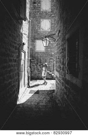 Monochrome Photo Of Young Woman Walking At Old Narrow Street