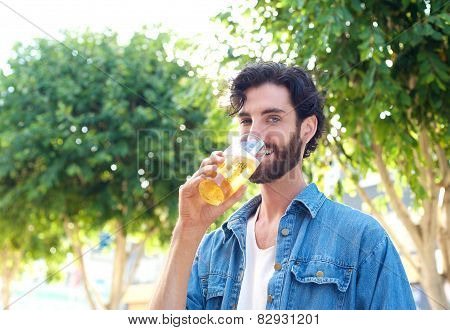 Man Enjoying A Drink Of Beer In Summer At Outdoor Bar