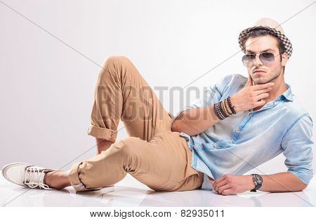 Handsome man lying on the floor, holding his hand to his chin, thinking.